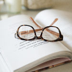 eye glasses on top of an open book