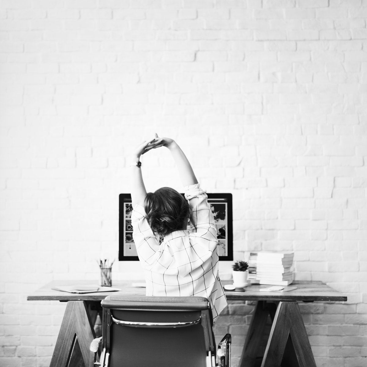 woman sitting at desk, stretching